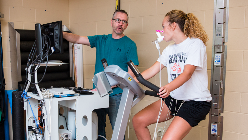 Dr. Ed Westen, Wartburg's new director of the Department of Health and Physical Education, monitors the cardiopulmonary functions of Emma Gerdes, a sophomore from Cedar Falls, during an exercising stress test.