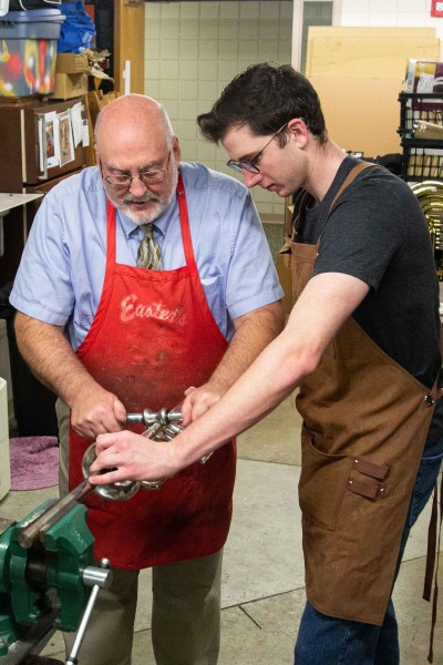 Garrett Arensdorf '20 and Dr. Craig Hancock work together to roll a dent out of an instrument.