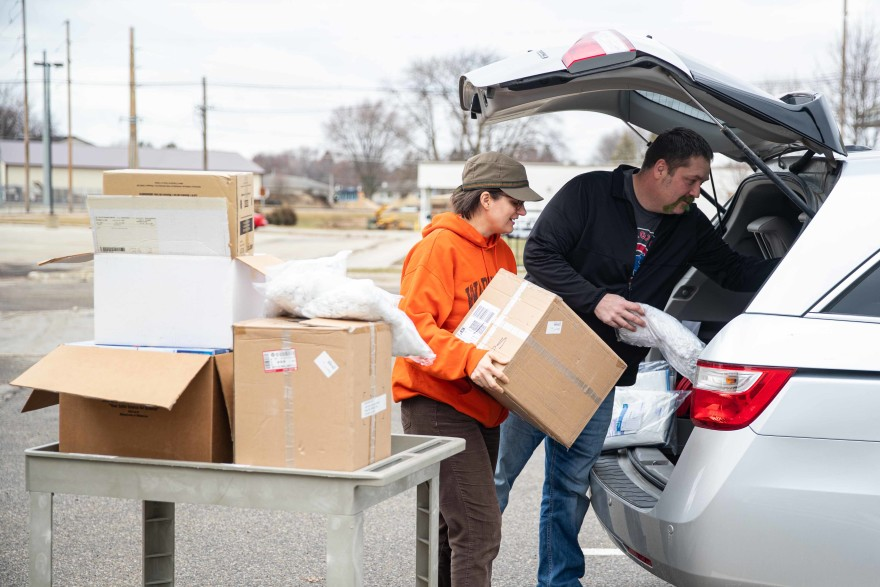 Christine DeVries and Eric Berns load unused personal protective equipment to be donated to the Waverly Health Center as they prepare for a surge in patients with COVID-19.