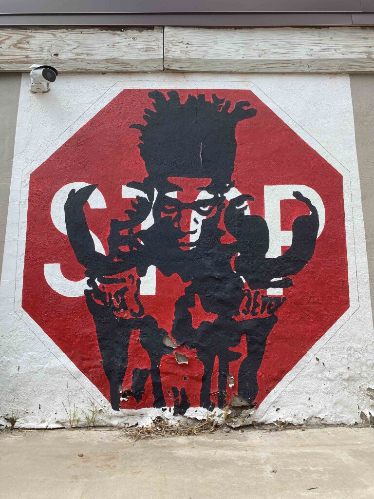 photo of painting of boxer Jean-Michel Basquiat painted on a stop sign on the side of a white building