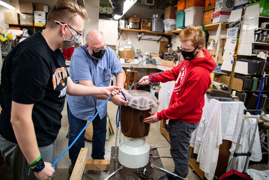 Dr. Craig Hancock (center), Chandler Njus (left) and Ezra Andersen assemble a taiko drum in the Wartburg College instrument repair room.